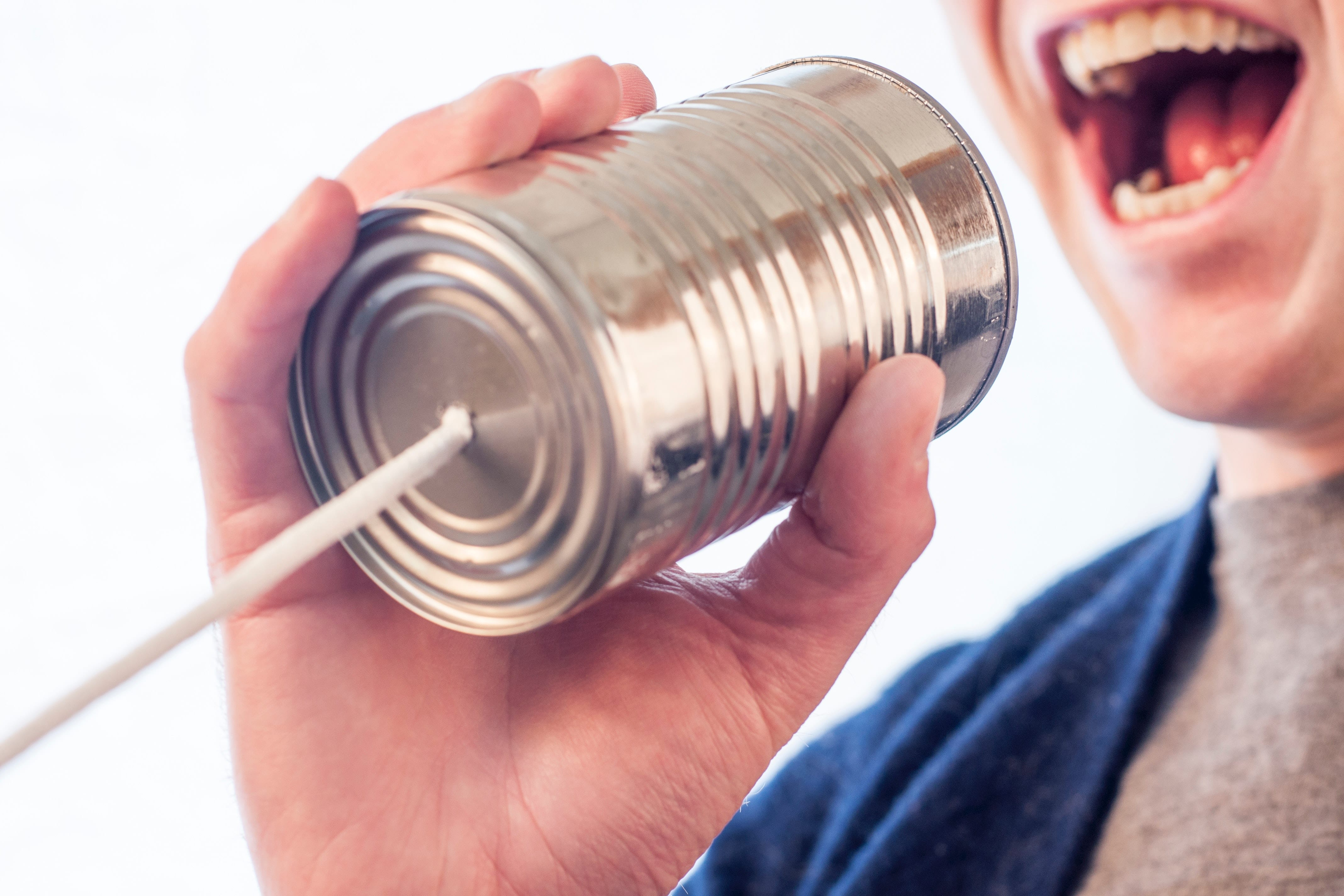 Photo: man speaking into can with a string attached