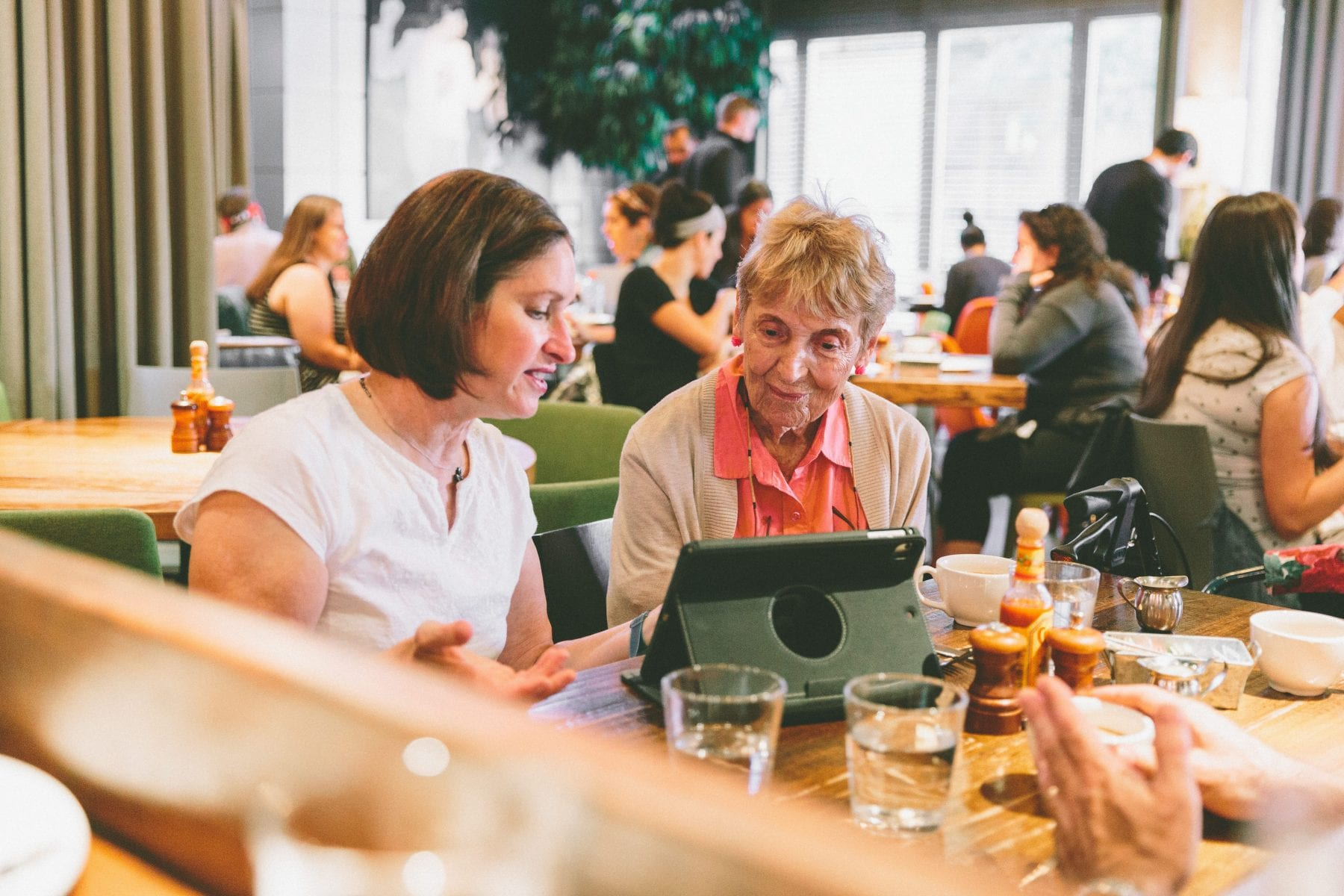 Photo: daughter helping her mom with a tablet in a coffee shop